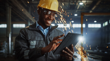 Professional Heavy Industry Engineer/Worker Wearing Safety Uniform and Hard Hat Uses Tablet Computer. Smiling African American Industrial Specialist Standing in a Metal Construction Manufacture.