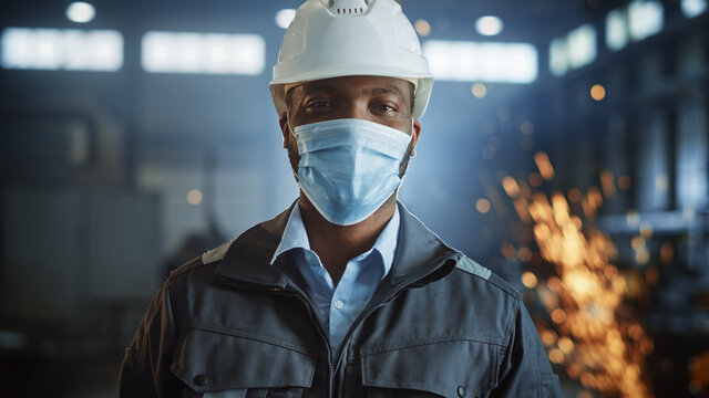 Professional Heavy Industry Engineer/Worker Wearing Safety Face Mask, Uniform and Hard Hat in a Steel Factory. African American Industrial Specialist Standing in a Metal Construction Manufacture.