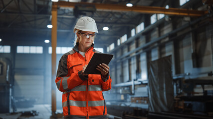 Professional Heavy Industry Engineer Worker Wearing Safety Uniform and Hard Hat, Using Tablet...