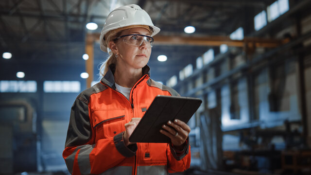Professional Heavy Industry Engineer/Worker Wearing Safety Uniform and Hard Hat Uses Tablet Computer. Serious Successful Female Industrial Specialist Walking in a Metal Manufacture Warehouse.