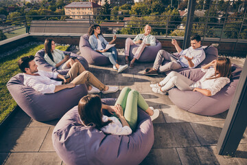 Fototapeta Nice attractive stylish partners leaders company unity sitting in bag chairs discussing project development on roof outside outdoor sunny day