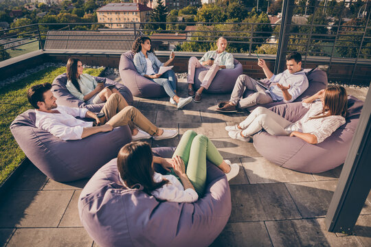 Nice attractive stylish partners leaders company unity sitting in bag chairs discussing project development on roof outside outdoor sunny day
