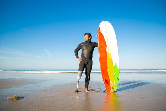 Confident handicapped man standing on sea beach with board. Attractive brunette man with artificial leg wearing black wetsuit and looking at ocean. Physical disability and extreme sport concept