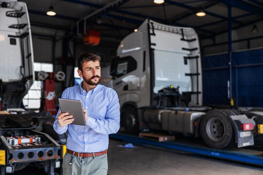 Young serious bearded CEO standing in garage of shipping firm and using tablet. In background are trucks.