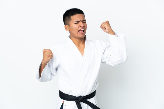 Young Ecuadorian man doing karate isolated on white background celebrating a victory