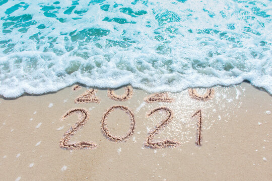 Message Year 2020 replaced by 2021 written on beach sand background. Good bye 2020 hello to 2021 happy New Year coming concept