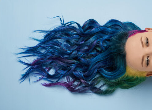 Girl with creative blue coloring and a rainbow in her hair on a blue background. Modern minimalistic bright photography for advertising and social networks