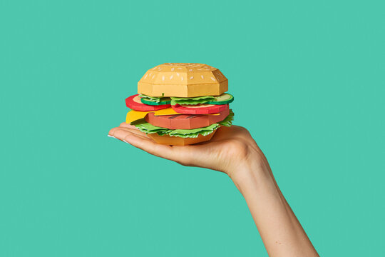 Hamburger made from paper on a hand.