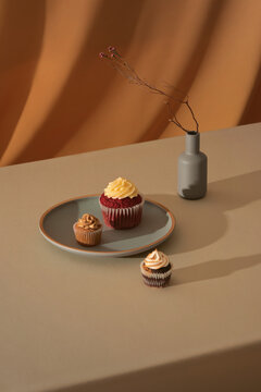 Cupcake on color table with phrase enjoy it and vase with flowers.