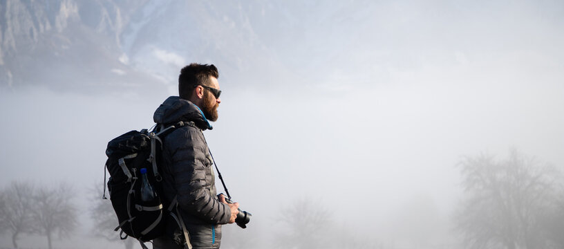 portrait of handsome man trekking in mountains in winter  outdoor adventure active lifestyle and social distancing space for your text