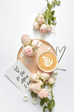 Paper card with coffee cup and roses .