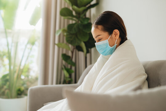 Asian woman with flu, sitting at home and wearing a mask.