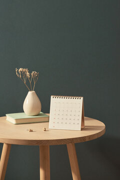 Calendar near the vase of flowers and book on wooden table