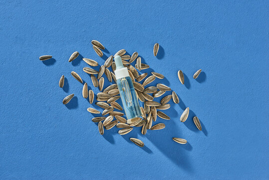 Natural organic sunflower oil in a bottle on a light background with seeds.
