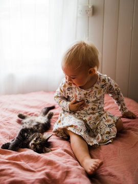 Little girl meets kitten for the first time
