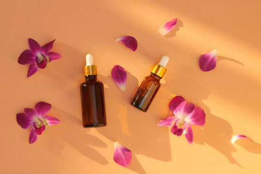 Different size and brown glass jars and bottles with massage and essential oils on bright color background. Beauty spa background concept.