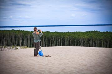 Fototapeta Dziewczyna robi zdjęcie telefonem na wydmach w Słowińskim Parku Narodowym, Łeba, Polska obraz