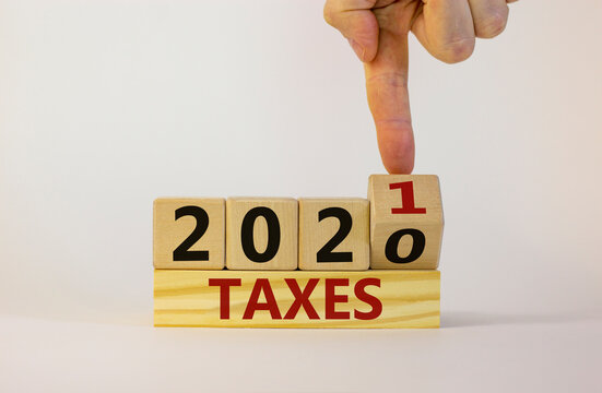 New year 2021 taxes. Male hand flips wooden cube and changes the inscription 'Taxes 2020' to 'Taxes 2021'. Beautiful white background, copy space. Business and 2021 new year taxes concept.