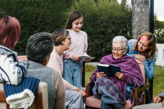 Mexican grandmother and family reading a book in a backyard outside home in Mexico city