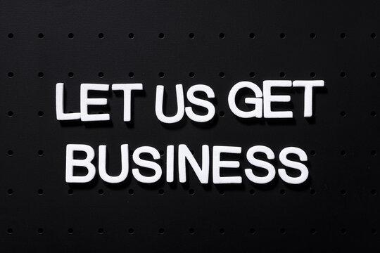 "Motivating inscription ""Let us get business"" written with white foam plastic letters"