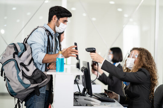 Caucasian male passenger handing phone to staff for check-in scanning.