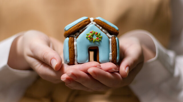 The pastry chef holds a Christmas gingerbread house in his palms. The symbol of the new year and merry christmas.