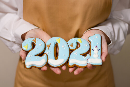 Pastry chef holds Christmas gingerbread in the form of 2021 numbers. New Year concept.