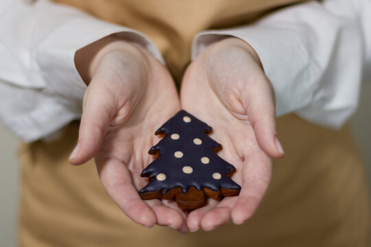 The pastry chef holds a gingerbread in the shape of a Christmas tree. The symbol of the new year and merry christmas.