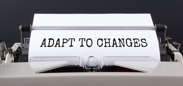 Text ADAPT TO CHANGES, typed on typewriter, close up. Motivational Business Concept.