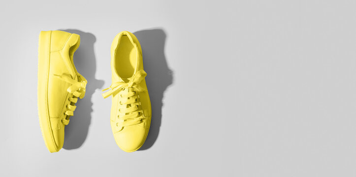 Banner with yellow female gumshoes on grey background. View from above. Space for text. Trendy color Ultimate Grey and Illuminating of the 2021 year.