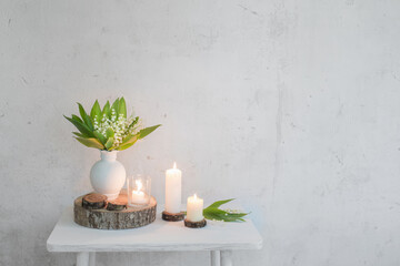 lily of the valley in vase with candles on background old white wall