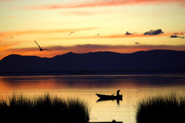 Wonderful sunrise on a lake with a fisherman in his boat and a bird flying towards the mountains in the background