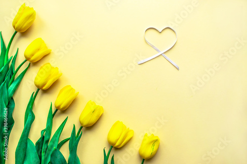 Sunny yellow spring flower arrangement. Yellow fresh tulips with heart on yellow paper background. Greeting card for Women's day, Mother's day, Valentine's Day or other holiday.