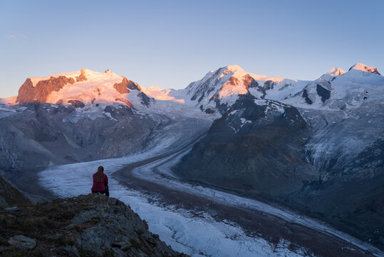 A woman looking over the Gorner glacier at the mountains during sunset.