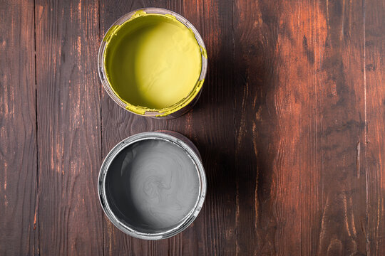 Cans with paint of ultimate gray and illuminating color on brown wooden background.