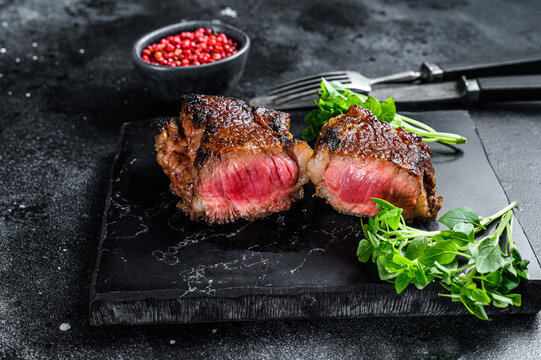 Grilled Striploin or new york steak. Black background. Top view