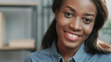 Close up portrait of young african american woman looking at camera with snow white smile sitting on office background. Fotomurales