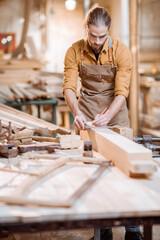Fototapeta Carpenter working with a wood in the workshop obraz