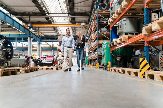 Female entrepreneur holding digital tablet walking with male colleague in industry