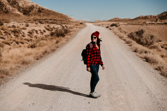 Spain, Navarre, Female tourist looking over shoulder in middle of empty dirt road in Bardenas Reales