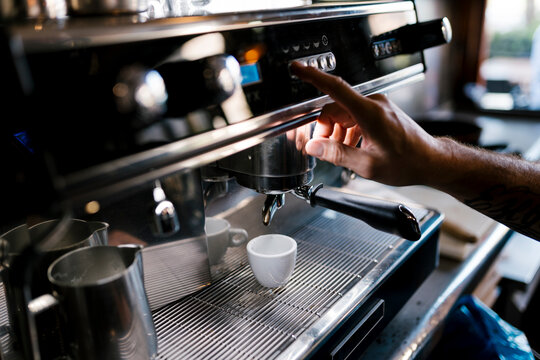 Male barista preparing coffee in cafe