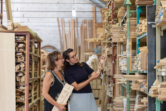 Female employee selecting ornate wood while standing in warehouse at factory