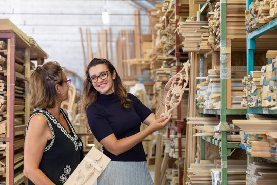 Interior designer choosing ornate design of wood panel while standing in factory