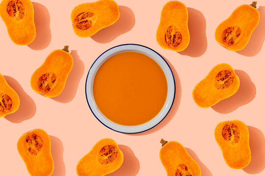 Studio shot of bowl of pumpkin soup surrounded by halves of butternut squash