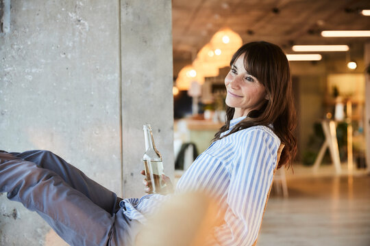 Smiling woman looking away while holding beer bottle sitting on chair at home