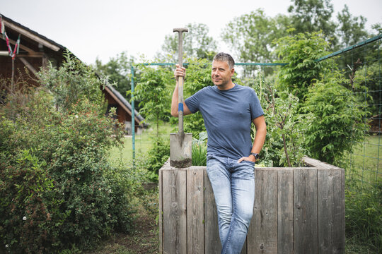 Handsome man holding spade looking away while leaning on wooden raised bed at vegetable garden