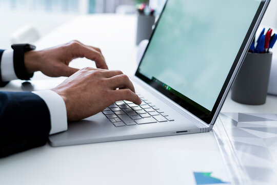 Hands of male professional tying on laptop keyboard at desk in workplace