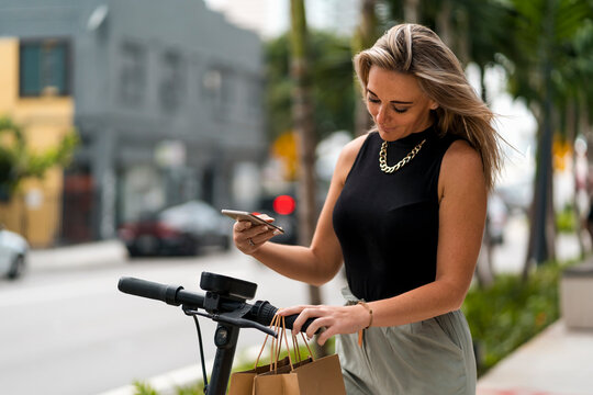 Woman scanning push scooter QR code with mobile phone while standing in city