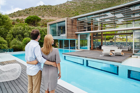 Heterosexual couple looking at modern house while standing outdoors