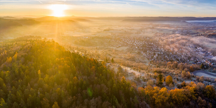 Drone view of autumn forest at foggy sunrise with village in background